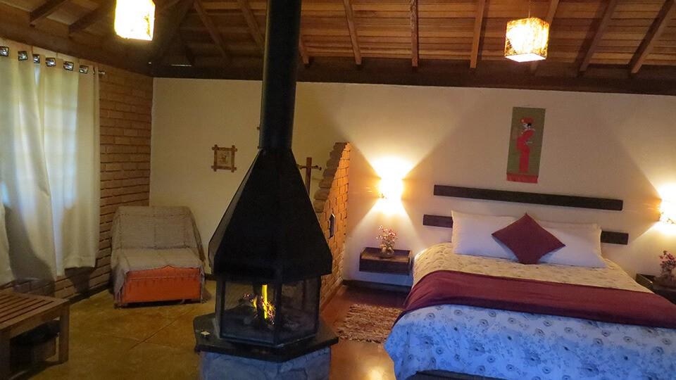 Interior do chalé Hidro: conforto, espaço, lareira e hidromassagem para você curtir os feriados de abril na Pousada Serra Vista em Gonçalves MG.